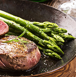 Venison steaks with buttered asparagus and red wine sauce